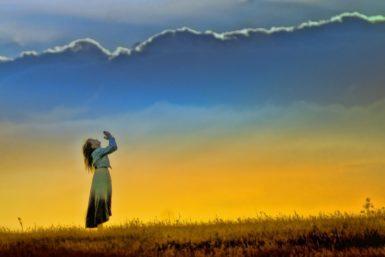 日没に祈る女性